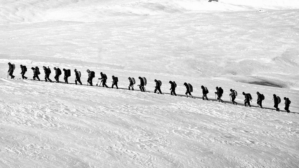A line of people in snow, indicating slow loading of queued resources in a browser